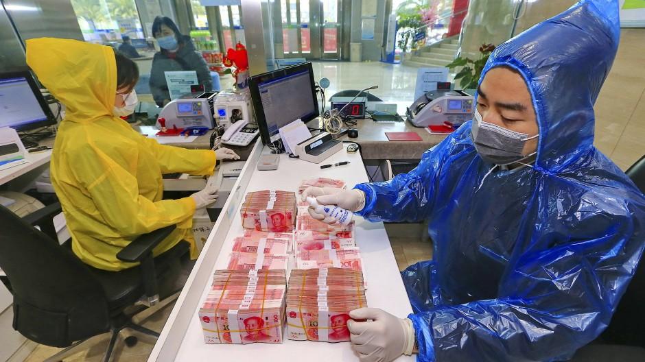Bargeld als Biotop: Chinesische Bankangestellte desinfizieren Banknoten, auf denen der Diktator Mao abgebildet ist.