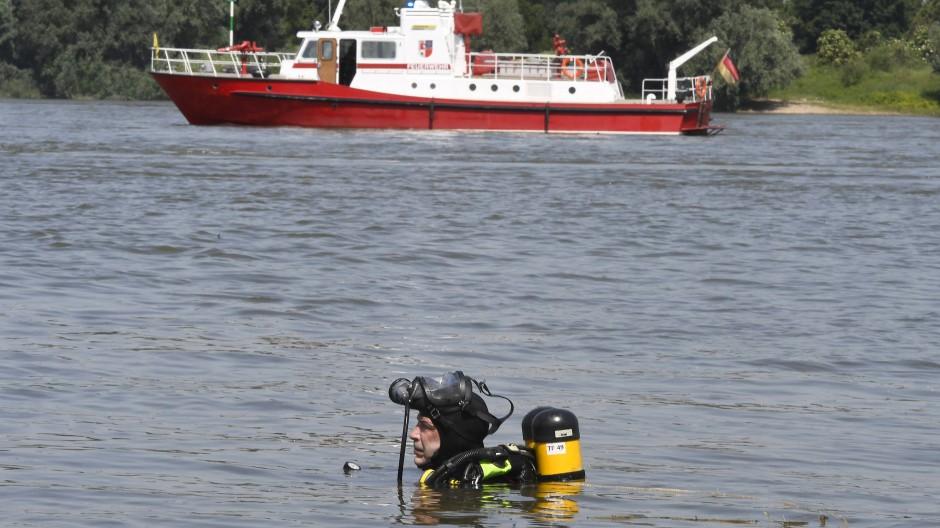 Ein Taucher der Feuerwehr sucht nach zwei vermissten Mädchen, die beim Baden im Rhein verunglückt sind.