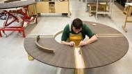 Interieur für Gutbetuchte: Ein Mitarbeiter montiert einen furnrierten Rundtisch.