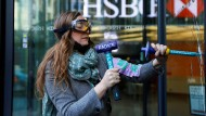 Eine Aktivistin schädigt ein Fenster der HSBC-Zentrale.