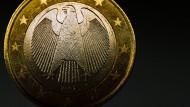 Eine deutsche Euromünze mit der Abbildung des Bundesadlers steht auf einem Tisch.