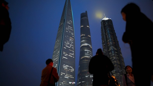 People walk on a bridge in the financial district of Pudong in Shanghai