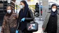 Auch Iran ist betroffen: Passantinnen gehen in Teheran mit Schutzmasken auf die Straße.