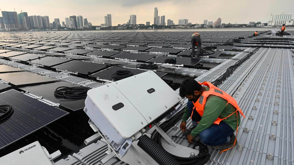 Singapur will umweltfreundlicher werden: Arbeiter verlegen Kabel für eine schwimmende Solaranlage auf See vor der Nordküste des Landes.