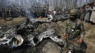 Indien, Budgam: Ein indischer Soldat geht an den Trümmern indischer Kampfflugzeuge vorbei.