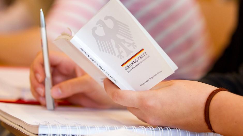 Eine Jura-Studentin hält in einer Vorlesung an der Universität Osnabrück eine Ausgabe vom Grundgesetz in der Hand (Archivbild).