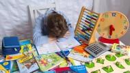 Ein frustrierter Schüler lernt Mathe. Vor ihm eine Auswahl an Hilfsmitteln