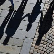 Eine Familie wirft lange Schatten auf das Pflaster.