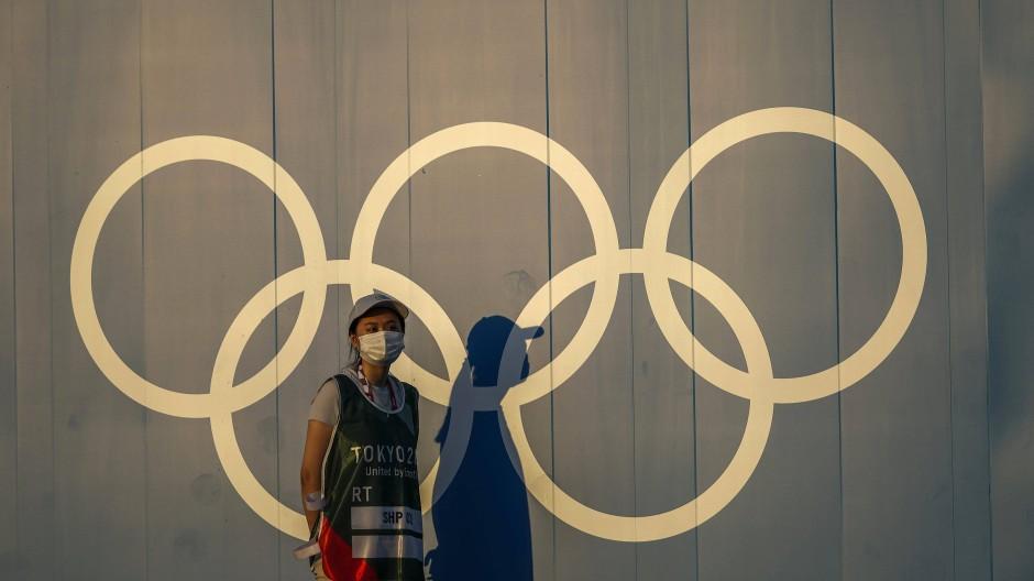 Ein Freiwilliger geht im Vorfeld der Olympischen Sommerspiele in Tokio am Logo der olympischen Ringe vorbei.