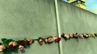 Rosen stecken in Berlin bei der Gedenkveranstaltung für die friedliche Revolution in der DDR 1989 an der Gedenkstätte Berliner Mauer in einem Spalt.