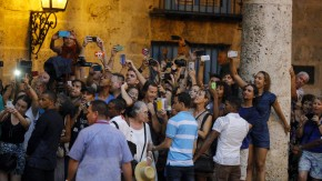 Tourists and local residents take pictures as U.S. President Barack Obama tours Old Havana with his family at the start of a three-day visit to Cuba, in Havana