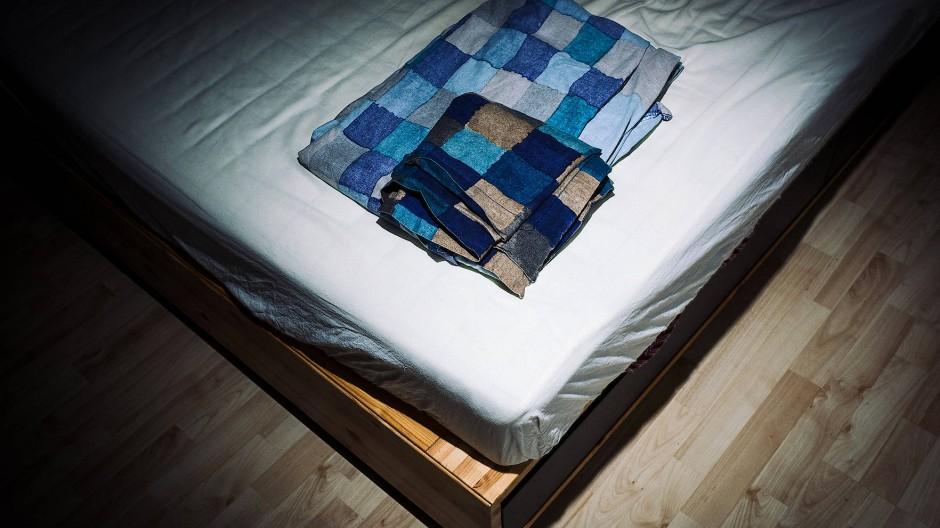 Zusammengelegte Bettbezüge auf einem nicht bezogenen Bett