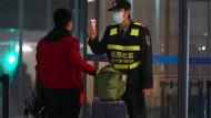 Ein Mitarbeiter am Flughafen in Wuhan misst bei einem Reisenden die Temperatur.