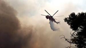 Ein Helikopter der Feuerwehr bekämpft den Waldbrand in Athen.