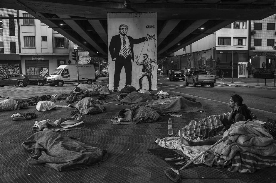 Einziger Schmuck in der Trostlostigkeit in einem Obdachlosenlager unter einer Überführung in der Innenstadt von São Paulo ist das Graffito am Brückenpfeiler. Es zeigt den amerikanischen Präsidenten Donald Trump, der mit dem brasilianischen Staatschef Jair Bolsonaro wie mit einer Marionette spielt. Die Zahl der Obdachlosen in Brasiliens größter und reichster Stadt ist in den letzten vier Jahren um 56 Prozent gestiegen.