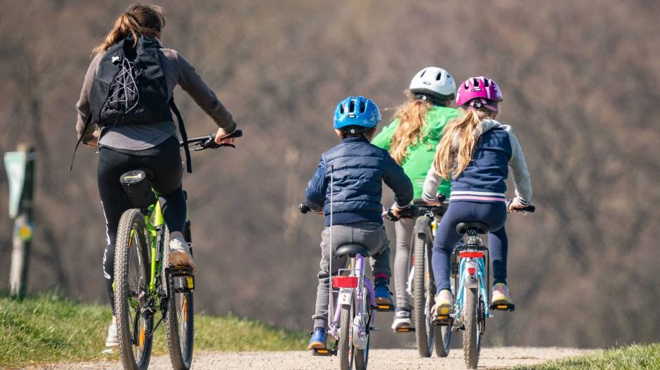 Eine Frau ist mit drei Kindern auf dem Fahrrad unterwegs auf einem Feldweg im Frankfurter Stadtteil Bergen.