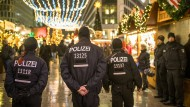 Polizisten gehen über den wiedereröffneten Weihnachtsmarkt am Breitscheidplatz in Berlin.