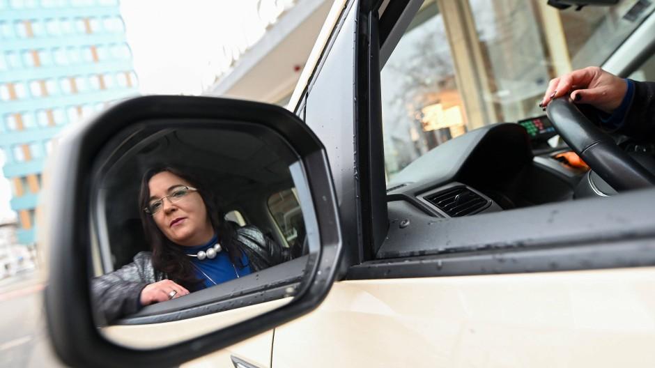 Taxifahrerin Beate Rößler sitzt vor einem Szenelokal in Kassel, Hessen, in ihrem Taxi.