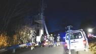 Einsatzkräfte stehen an dem Strommast, auf dem ein deutscher Jugendlicher geklettert und zu Tode gekommen ist.
