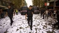 Katalanische Polizisten gehen am 3. Oktober in Barcelona über eine Straße auf der Wahlzettel des Unabhängigkeitsreferendums liegen.