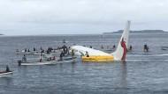 Anwohner der Insel helfen mit Fischerbooten die Passagiere und Besatzung des Flugzeuges an Land zu bringen.