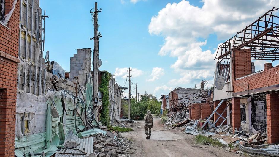 Ein ukrainischer Soldat geht durch das völlig zerstörte Dorf Schyrokyne.