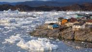 Bunte Holzhäuser am Meer mit Bruchstücken eines Eisbergs in Ilulissat