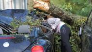 Tornado-Opfer: Eine Frau klaubt im August ihre Habseligkeiten aus ihrem zerstörten Auto in Bad Schwalbach