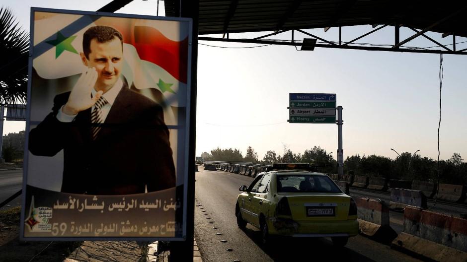 Gefährliche Heimat: Ein Poster von Machthaber Baschar al Assad auf der Straße zum Flughafen von Damaskus