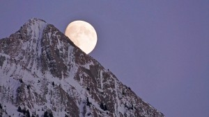 A near full moon rises behind the majestic Rocky Mountain, near Jasper...