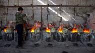 Ein Arbeiter rührt Kessel voll Seltener Erden in einer Werkstatt in der Nähe von Damao im Norden Chinas an der Grenze zur Mongolei.