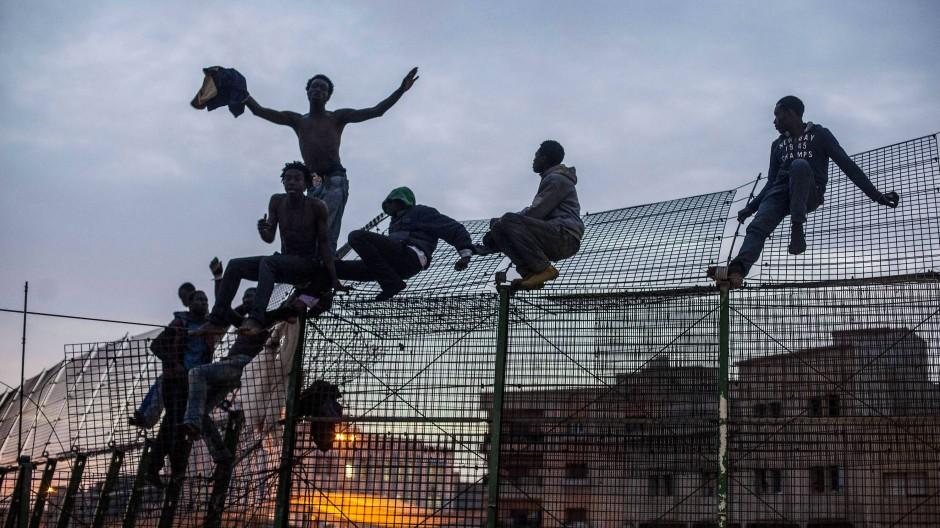 Asylsuchende beim Übersteigen des Grenzzauns zur spanischen Exklave Melilla am 28. März 2014.