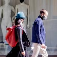 Ein Mann und eine Frau laufen mit Schutzmasken in Berlin an einem Schaufenster vorbei.