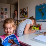 Auch beim Homeschooling gibt es Hausaufgaben: Charlotte, 12 Jahre, und Franziska, 10 Jahre, arbeiten in ihrem Tempo. Matilda, 3 Jahre, leistet Gesellschaft, und Mutter Stephanie Machnik schaut nach dem Rechten.