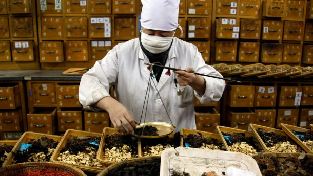 A worker in the herbal medicine department of the Beijing University Hospital of Chinese Medicine, weighs and then mixes herbs for packaging