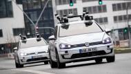 Zwei autonome VW-Elektro-Golf-Testwagen fahren durch Hamburg.