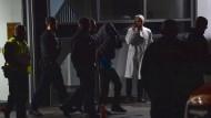 Polizisten führen die festgenommene Person an einer Privatklinik in Berlin-Charlottenburg ab.