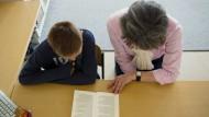 Eine Lesepatin hilft einem Schüler beim Textverständnis.