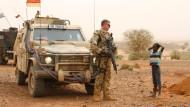 Ein deutscher Blauhelmsoldat unterhält sich während einer Patrouille am 7. Mai 2016 in der Stadt Gao im Norden Malis mit einem Kind