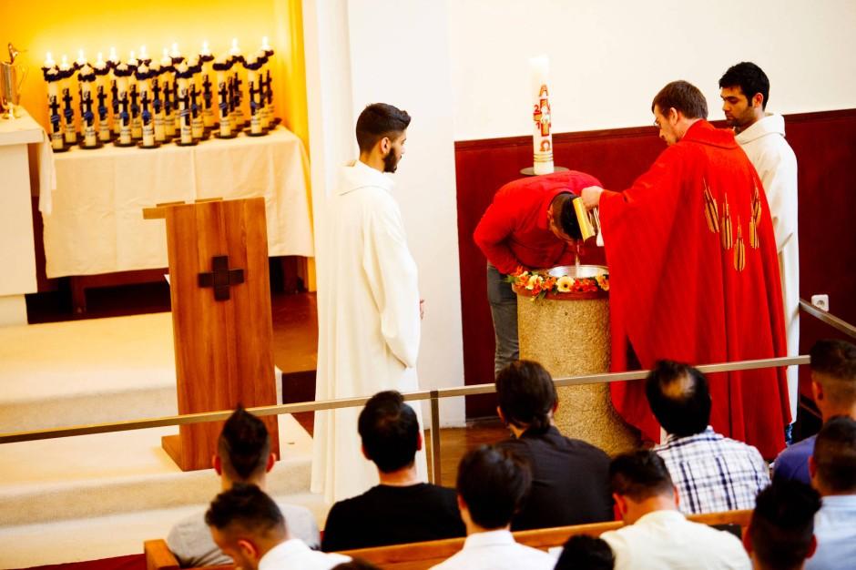 Pfarrer Martens tauft einen von 24 Flüchtlingen.