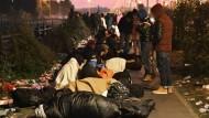 Nach einer Nacht im Freien: Flüchtlinge am Donnerstagmorgen in der Nähe des geräumten Camps