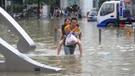 Ein Mann trägt eine Frau durch die Straßen von Zhengzhou.