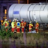 Rettungskräfte und Ermittler stehen neben den abgedeckten Leichen am Kesselwagen.