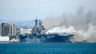 """Rauch steigt von der """"USS Bonhomme Richard"""" auf, während Löschbote im Einsatz sind."""