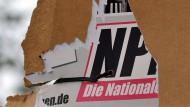 Ein zerrissenes Wahlplakat der NPD hängt an einem Laternenmast (Archivbild).