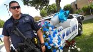 Ein Polizist steht vor einem mit Blumen geschmückten Polizeiauto in Dallas, Texas. In der Nacht zuvor waren dort fünf Polizisten von einem Heckenschützen getötet worden.