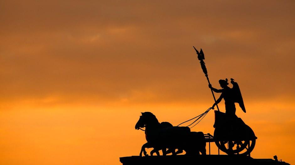 Berliner Wahrzeichen und deutsches Nationalsymbol: Die Quadriga des Brandenburger Tors im Sonnenaufgang