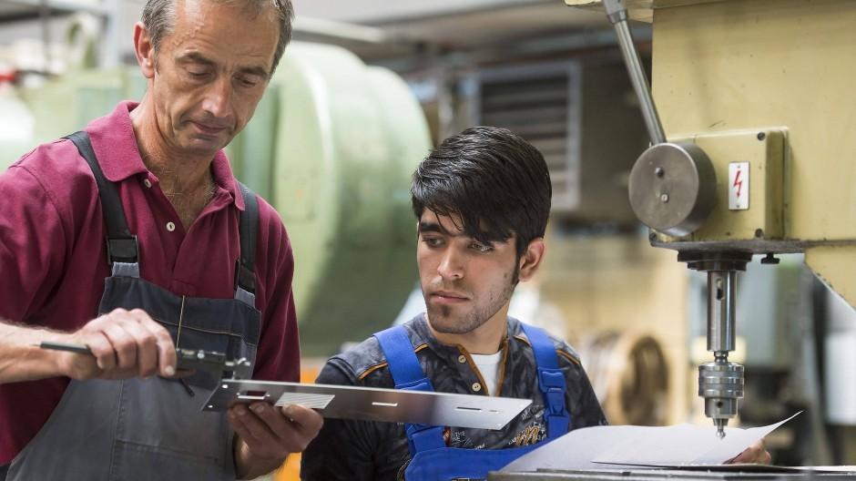 Ein Ausbilder mit einem Flüchtling im Jahr 2016. Integrationserfolge auf dem Arbeitsmarkt sind gefährdet, sagt die OECD.