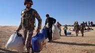 Jordanische Soldaten helfen Flüchtlingen aus Syrien. Nach Angaben der UNO beherbergt das Land mehr als 630.000 syrische Kriegsflüchtlinge.