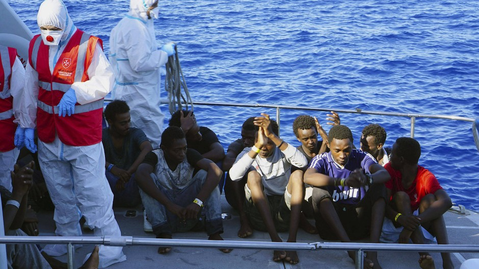 """Flüchtlinge werden am Samstag von der italienischen Küstenwache von der """"Open Arms"""" an Land gebracht"""